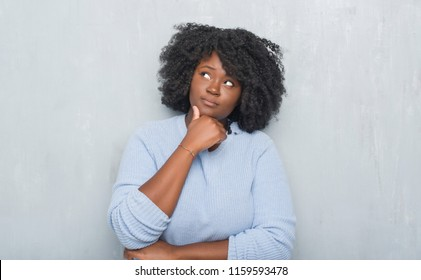 Young african american woman over grey grunge wall wearing winter sweater with hand on chin thinking about question, pensive expression. Smiling with thoughtful face. Doubt concept.