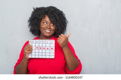 Young african american woman over grey grunge wall holding menstruation calendar pointing and showing with thumb up to the side with happy face smiling
