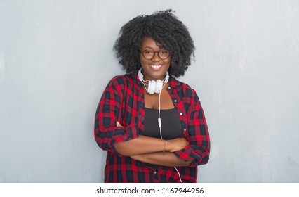 Young african american woman over grey grunge wall wearing headphones happy face smiling with crossed arms looking at the camera. Positive person.