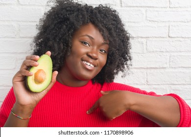 Young african american woman over white brick wall eating avocado with surprise face pointing finger to himself