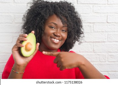 Young african american woman over white brick wall eating avocado very happy pointing with hand and finger