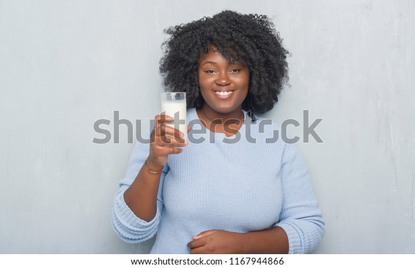 Young african american woman over grey grunge wall drinking a glass of milk with a happy face standing and smiling with a confident smile showing teeth