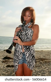 a young african american woman plays her clarinet outside at the beach for all to hear and enjoy