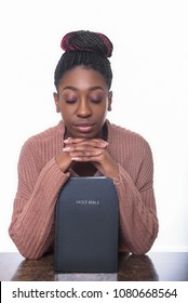A young African American woman praying over the Holy Bible