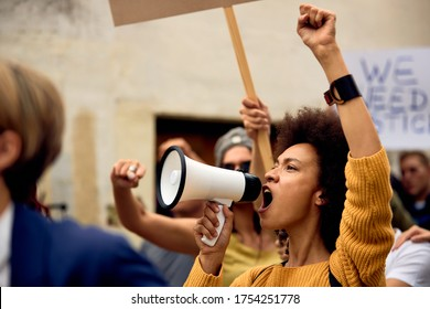 Young African American woman with raised fist shouting through megaphone while being on anti-racism protest.