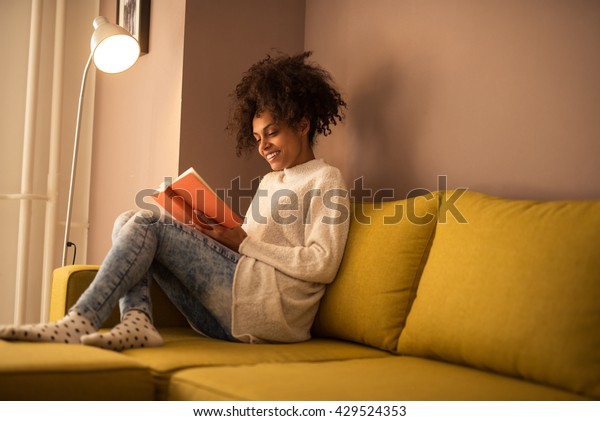 Young african american woman reading a book at home.