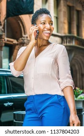 Young African American Woman with short afro hair traveling in New York, wearing pink V neck shirt, blue pants, walking on narrow vintage street, looking around, talking on cell phone, smiling.