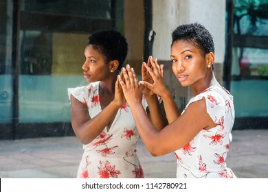 Young African American Woman with short afro hairstyle, standing by mirror in New York, hands touching reflections, head turning around, thinking. Concept of self assured, self esteem, self checking.
