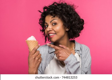 Young African american woman showing at ice cream and smiling isolated on pink