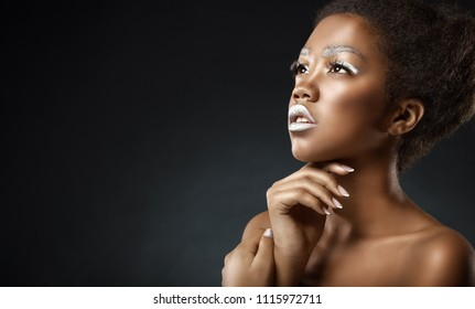 Young African American woman with silver make-up on a black background