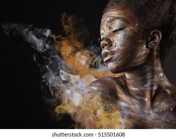 Jovem Africano Americano mulher com prata e ouro maquiagem e arte corporal em um fundo preto com fumaça