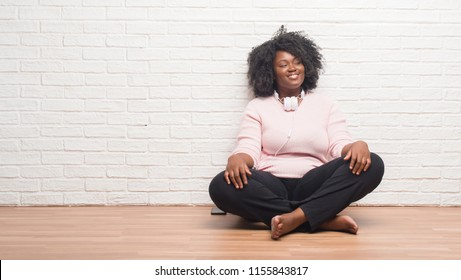 Young african american woman sitting on the floor wearing headphones looking away to side with smile on face, natural expression. Laughing confident.