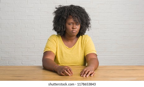 Young african american woman sitting on the table at home skeptic and nervous, frowning upset because of problem. Negative person.