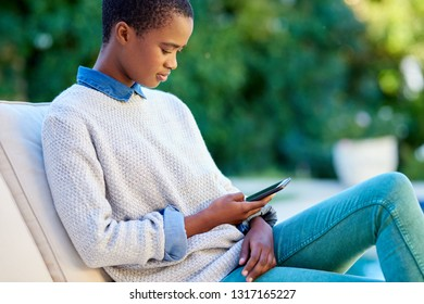 Young African American woman sitting outside on her patio at home reading a text message on her cellphone