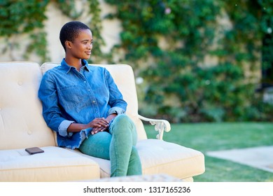 Young African American woman smiling while sitting on a sofa outside on her patio on a sunny day