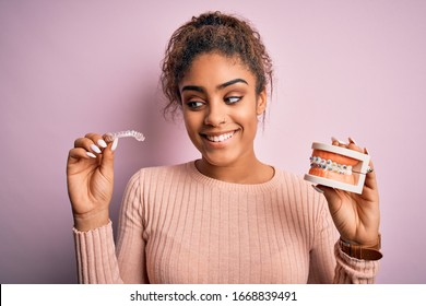 Young african american woman smiling happy holding professional orthodontic denture with metal braces and removable invisible aligner. Comparation of two dental straighten treatments