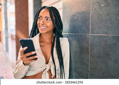 Young african american woman smiling happy using smartphone at the city.