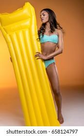 young african american woman in swimwear holding yellow swimming mattress