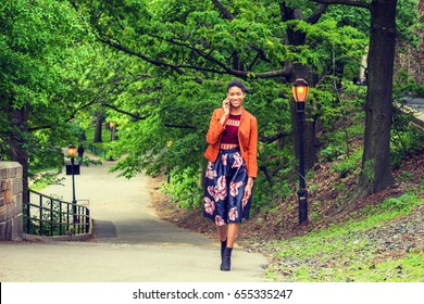 Young African American Woman talking on cell phone outside in New York, wearing orange red jacket, dark purple flower patterned skirt, black boot shoes, walking up on small road with green trees.