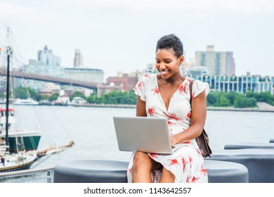 Young African American Woman traveling in New York, with short afro hair, wearing dress, carrying bag, sitting by river, working on laptop computer. Brooklyn, Manhattan bridges, boat on background.