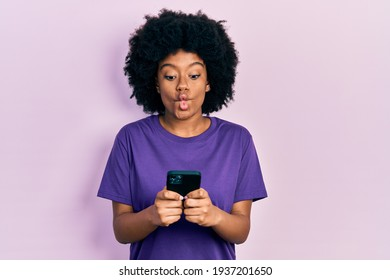 Young african american woman using smartphone typing message making fish face with mouth and squinting eyes, crazy and comical.