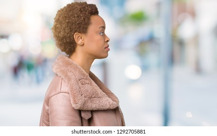 Young african american woman wearing winter coat over isolated background looking to side, relax profile pose with natural face with confident smile.