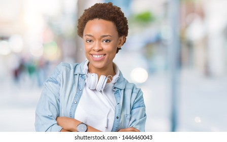 Young african american woman wearing headphones over isolated background happy face smiling with crossed arms looking at the camera. Positive person.