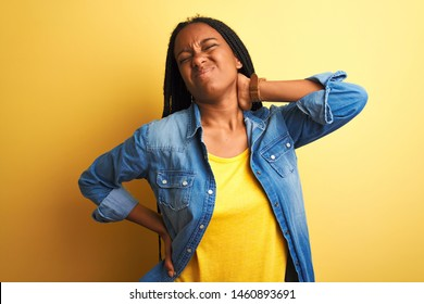 Young african american woman wearing denim shirt standing over isolated yellow background Suffering of neck ache injury, touching neck with hand, muscular pain