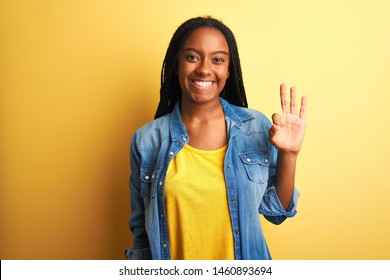 Young african american woman wearing denim shirt standing over isolated yellow background showing and pointing up with fingers number three while smiling confident and happy.