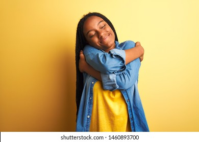 Young african american woman wearing denim shirt standing over isolated yellow background Hugging oneself happy and positive, smiling confident. Self love and self care