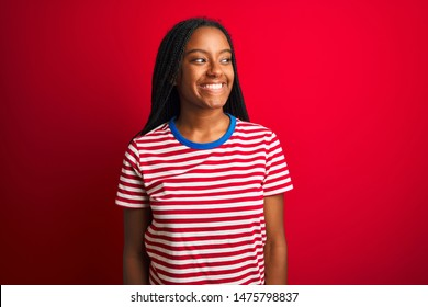 Young african american woman wearing striped t-shirt standing over isolated red background looking away to side with smile on face, natural expression. Laughing confident.