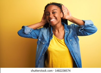 Young african american woman wearing denim shirt standing over isolated yellow background Trying to hear both hands on ear gesture, curious for gossip. Hearing problem, deaf