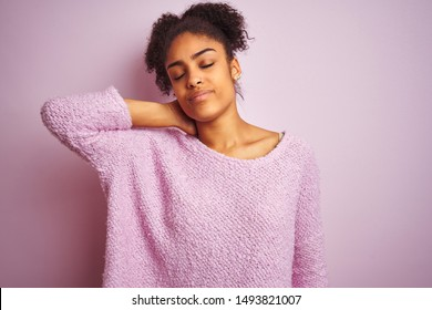 Young african american woman wearing winter sweater standing over isolated pink background Suffering of neck ache injury, touching neck with hand, muscular pain