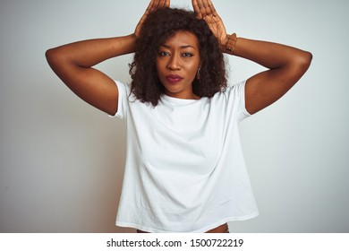 Young african american woman wearing t-shirt standing over isolated white background Doing bunny ears gesture with hands palms looking cynical and skeptical. Easter rabbit concept.