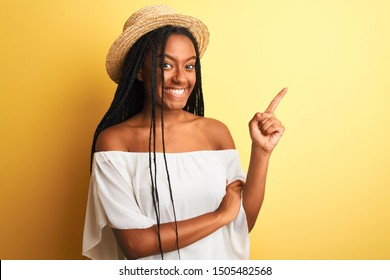 Young african american woman wearing white t-shirt and hat over isolated yellow background with a big smile on face, pointing with hand and finger to the side looking at the camera.