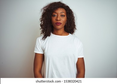 Young african american woman wearing t-shirt standing over isolated white background Relaxed with serious expression on face. Simple and natural looking at the camera.