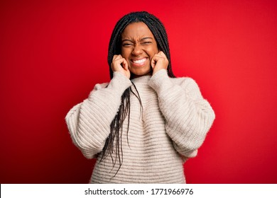 Young african american woman wearing casual winter sweater over red isolated background covering ears with fingers with annoyed expression for the noise of loud music. Deaf concept.