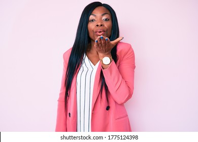 Young african american woman wearing business clothes looking at the camera blowing a kiss with hand on air being lovely and sexy. love expression.