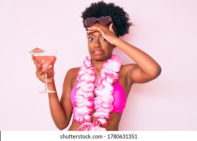 Young african american woman wearing bikini and hawaiian lei holding cocktail stressed and frustrated with hand on head, surprised and angry face