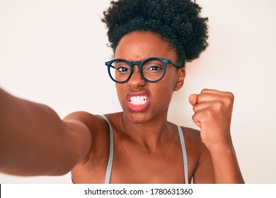 Young african american woman wearing casual clothes and glasses making selfie by the camera annoyed and frustrated shouting with anger, yelling crazy with anger and hand raised