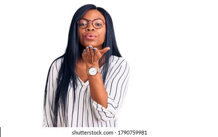 Young african american woman wearing casual clothes and glasses looking at the camera blowing a kiss with hand on air being lovely and sexy. love expression.