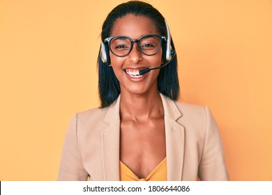 Young african american woman wearing call center agent headset smiling and laughing hard out loud because funny crazy joke.