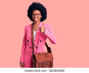 Young african american woman wearing business clothes and leather bag smiling happy and positive, thumb up doing excellent and approval sign