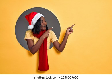 Young african american woman wearing christmas hat and scarf pointing to side. Christmas sale concept. Copy space.