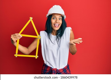Young african american woman wearing architect hardhat holding build project celebrating achievement with happy smile and winner expression with raised hand