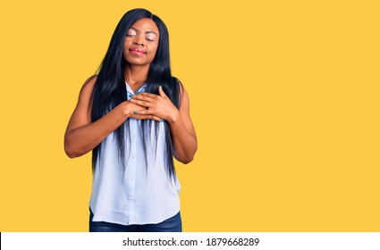 Young african american woman wearing casual clothes smiling with hands on chest with closed eyes and grateful gesture on face. health concept.