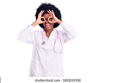 Young african american woman wearing doctor coat and stethoscope doing ok gesture like binoculars sticking tongue out, eyes looking through fingers. crazy expression.