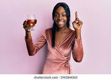 Young african american woman wearing sexy party dress holding cocktail surprised with an idea or question pointing finger with happy face, number one