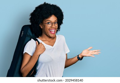 Young african american woman wearing guitar case celebrating achievement with happy smile and winner expression with raised hand