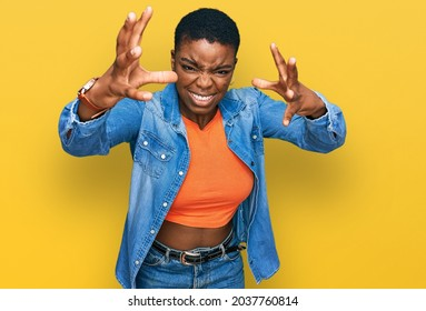 Young african american woman wearing casual clothes shouting frustrated with rage, hands trying to strangle, yelling mad